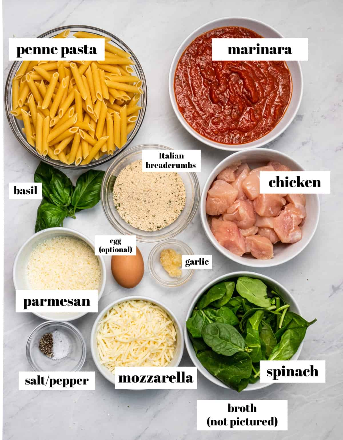 Pasta, marinara, cheese and other ingredients labeled on counter.