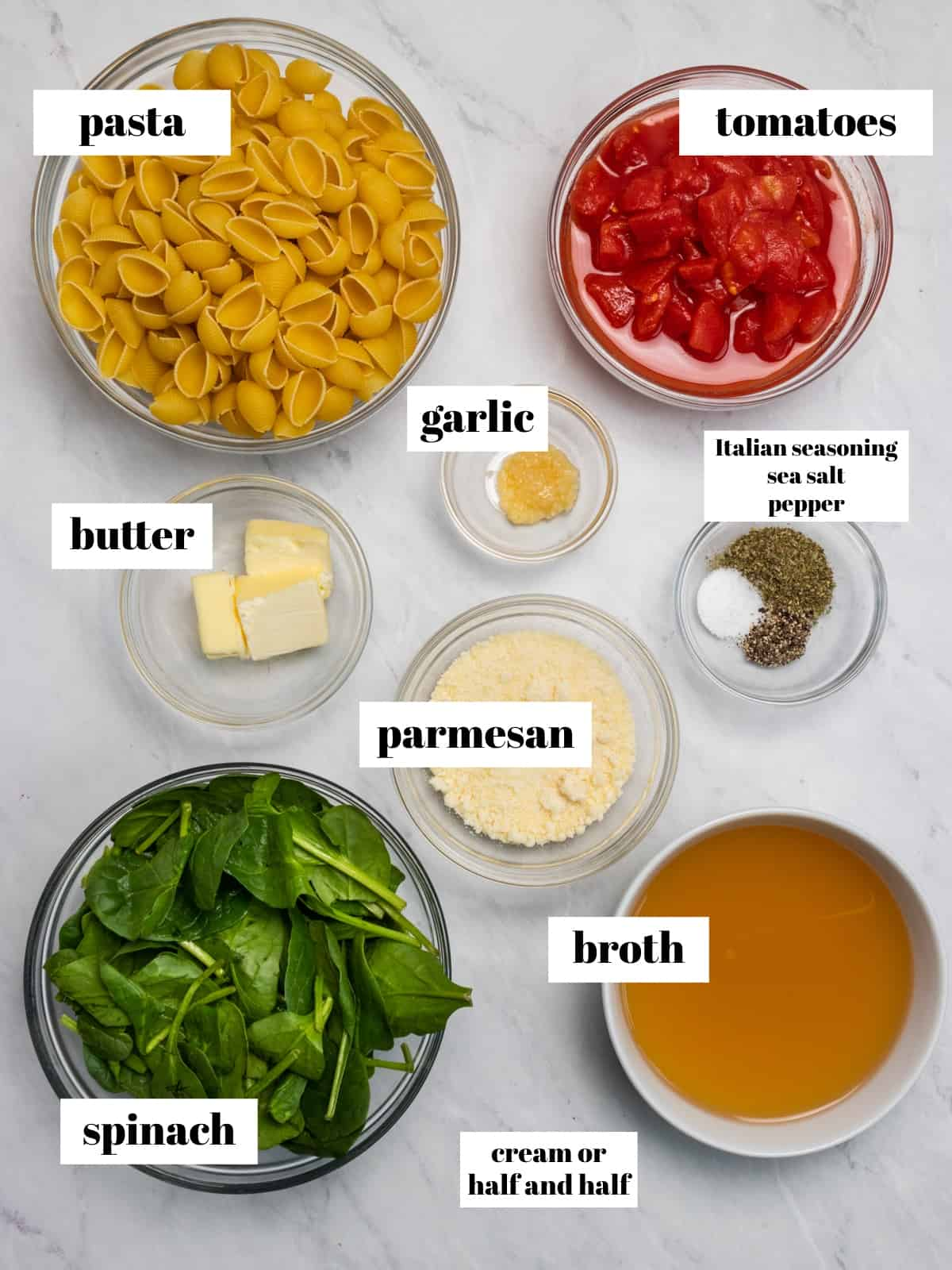 Spinach, broth, tomatoes, cheese and ingredients labeled on counter.
