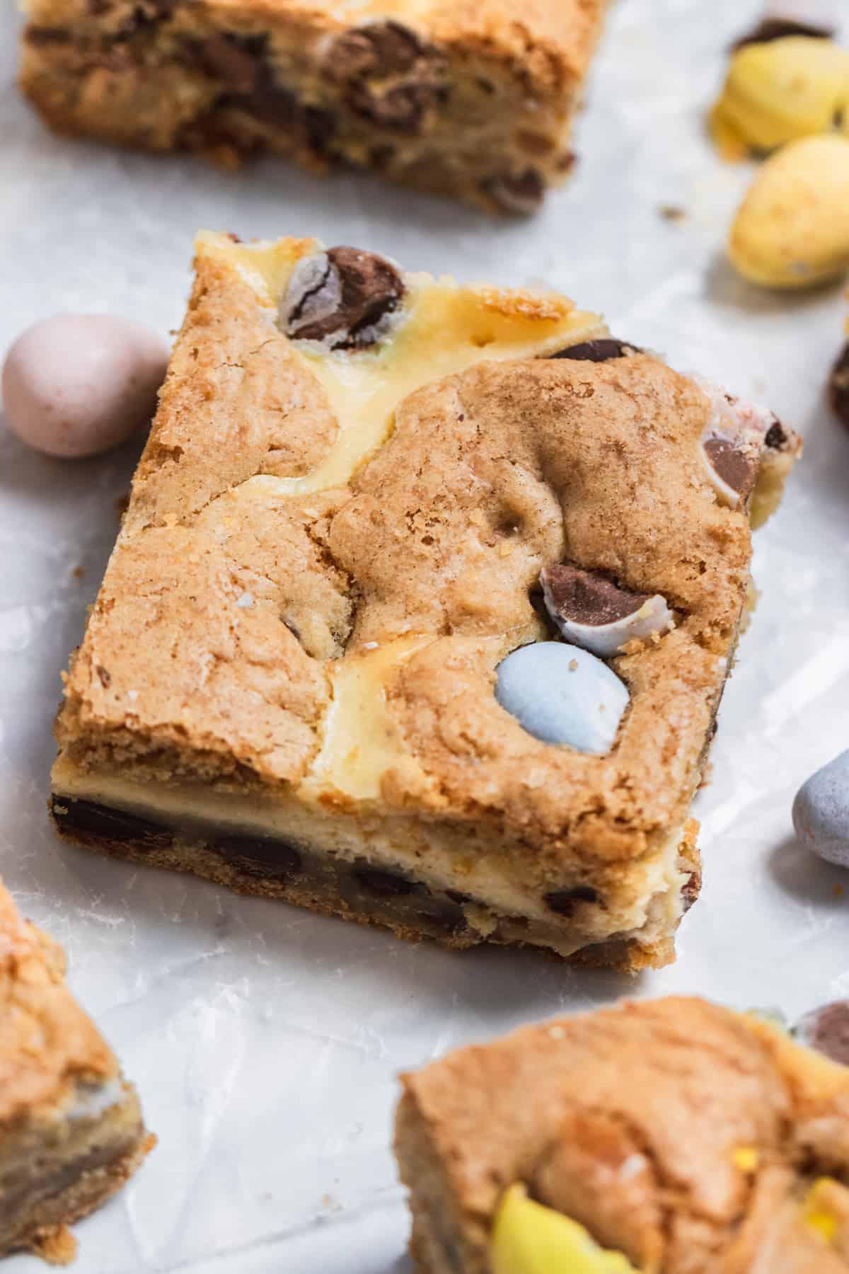 Mini egg cheesecake cookie bars on wax paper.