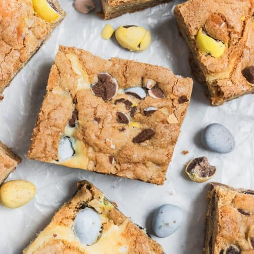 Mini egg cheesecake cookie bars on wax paper with eggs surrounding.