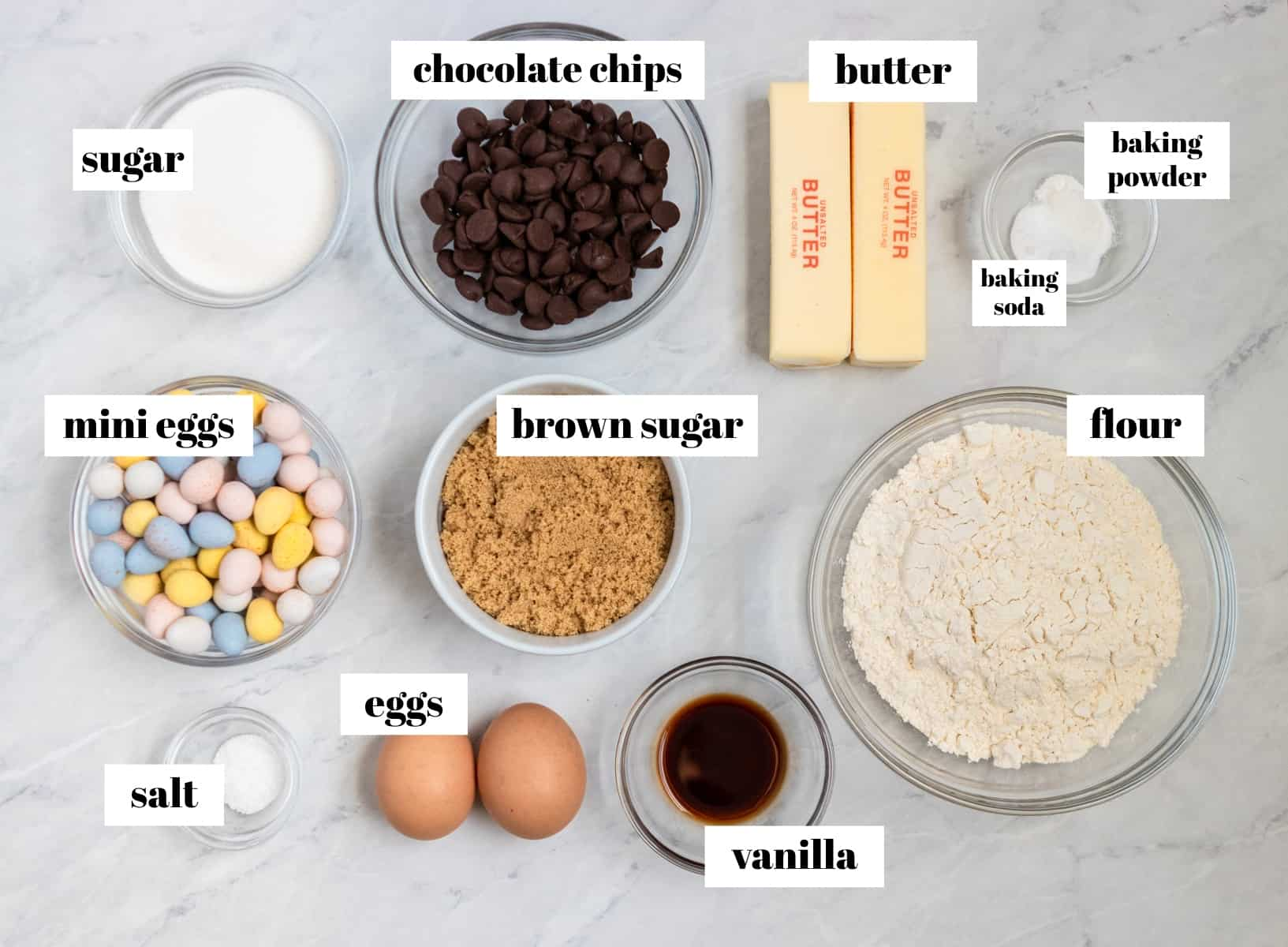 Flour, eggs, chocolate chips and other ingredients labeled on counter.