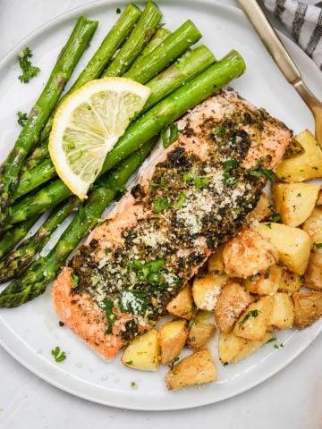 Overhead of pesto salmon on plate with potatoes.