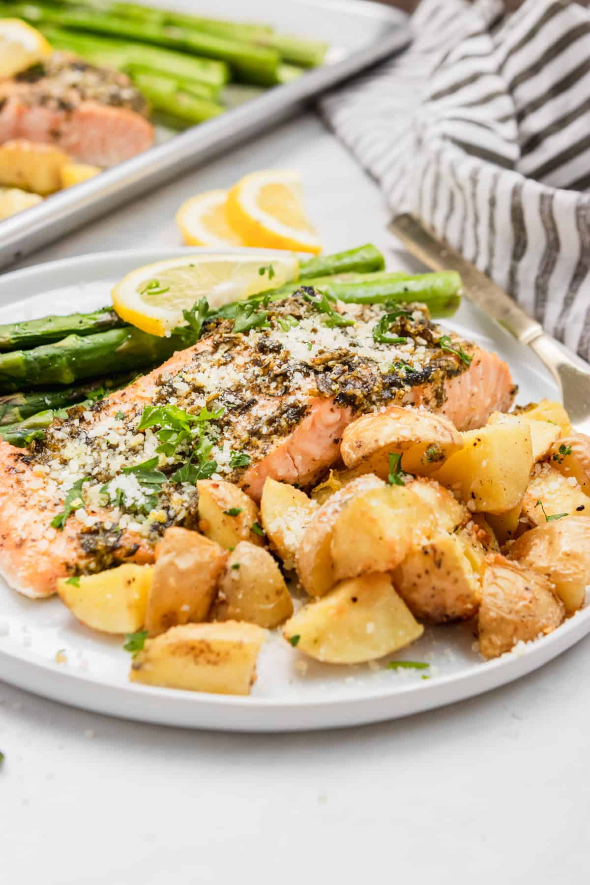 Pesto salmon, potatoes and asparagus on white plate with sheet pan in background.
