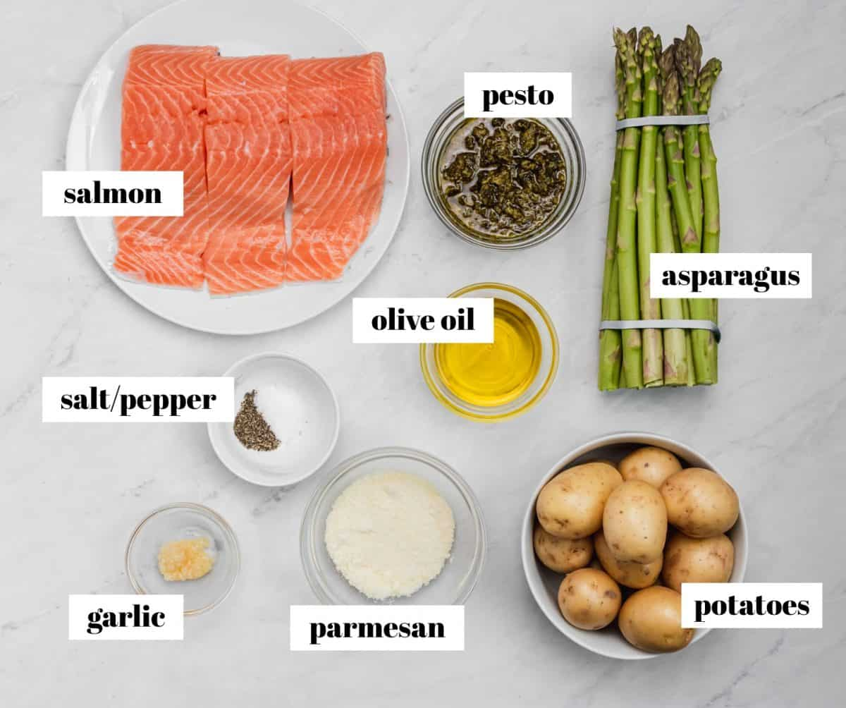 Salmon, asparagus, parmesan, potatoes and other ingredients labeled on counter.
