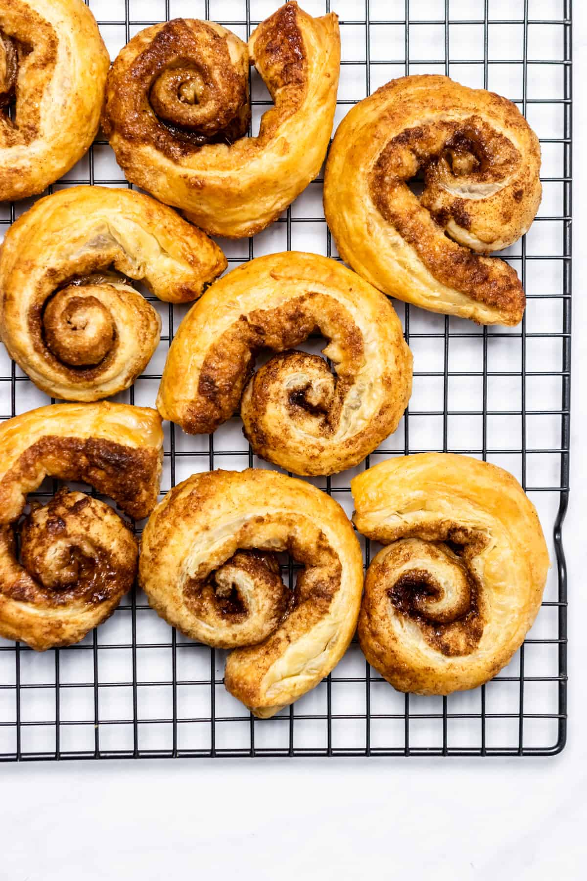 Puff pastry cinnamon rolls cooling on cooling rack.