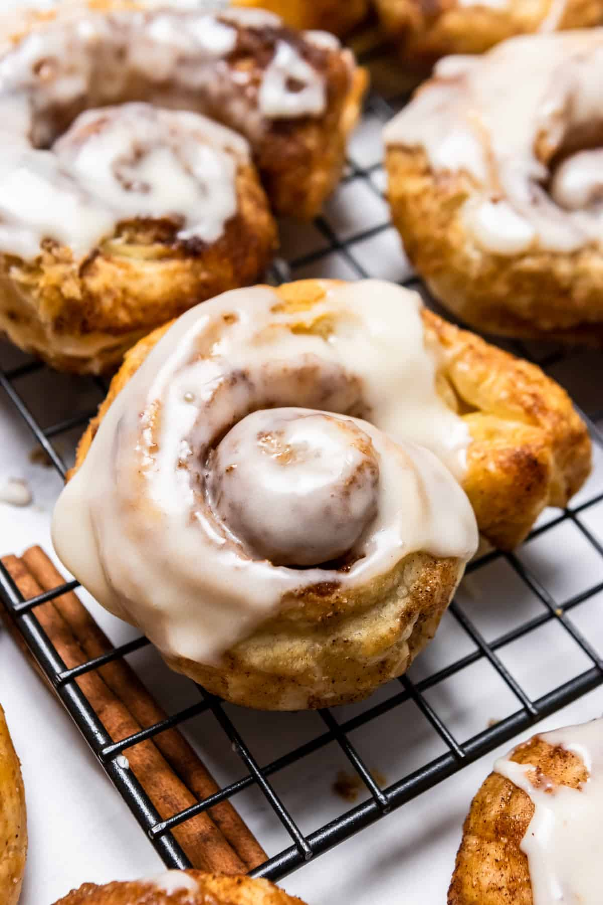 Puff pastry Cinnamon rolls with icing on cooling rack.