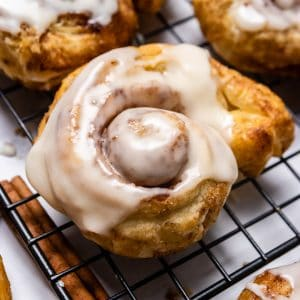 Puff Pastry Cinnamon roll with icing on cooing rack.