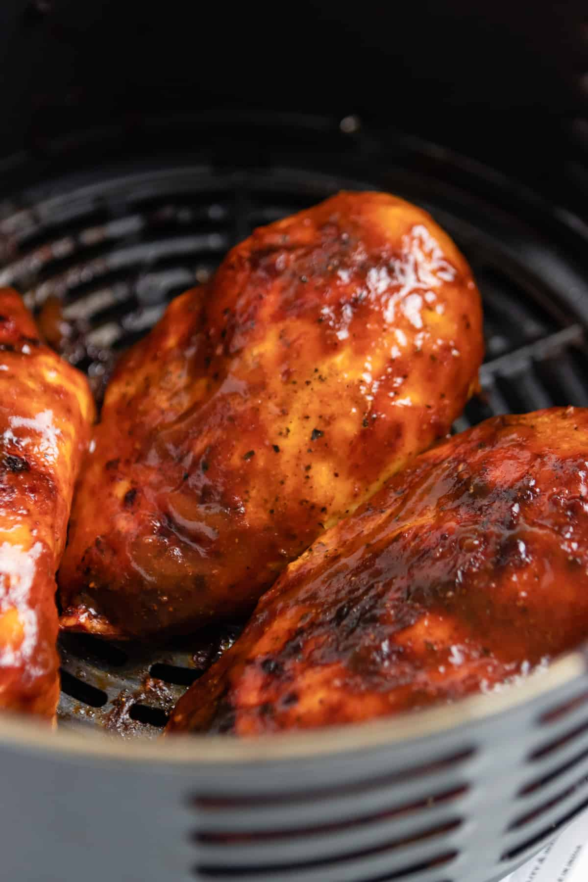 BBQ sauce on chicken in air fryer.