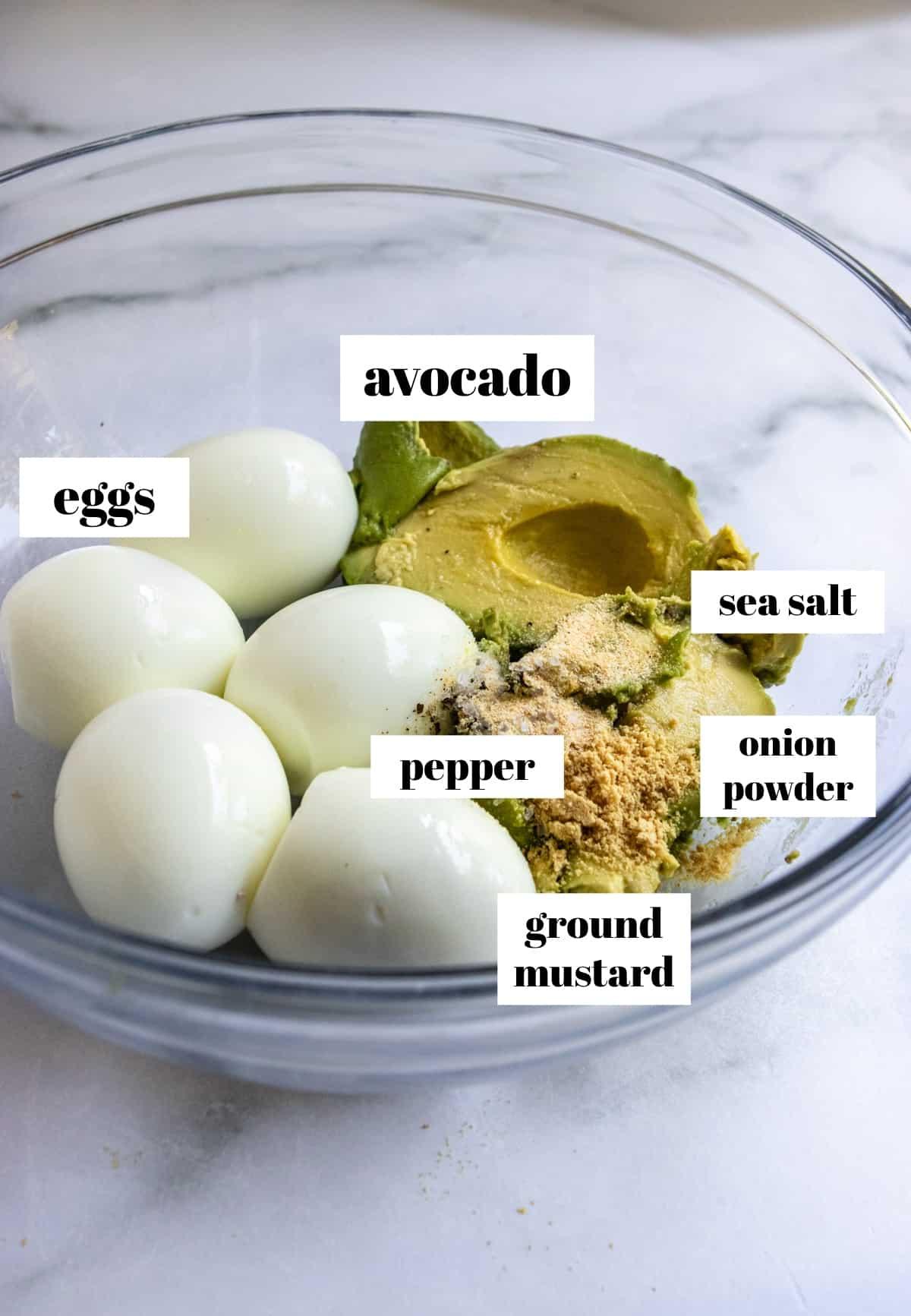 Eggs, avocado, seasonings in glass mixing bowl.