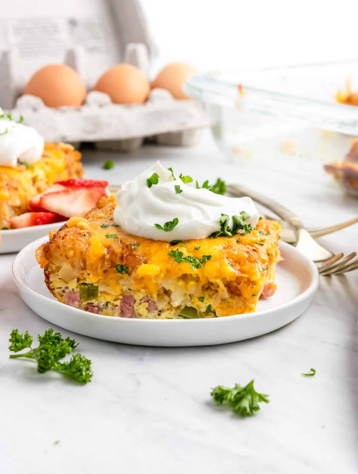 Breakfast casserole with tator tots with sour cream on white plate.