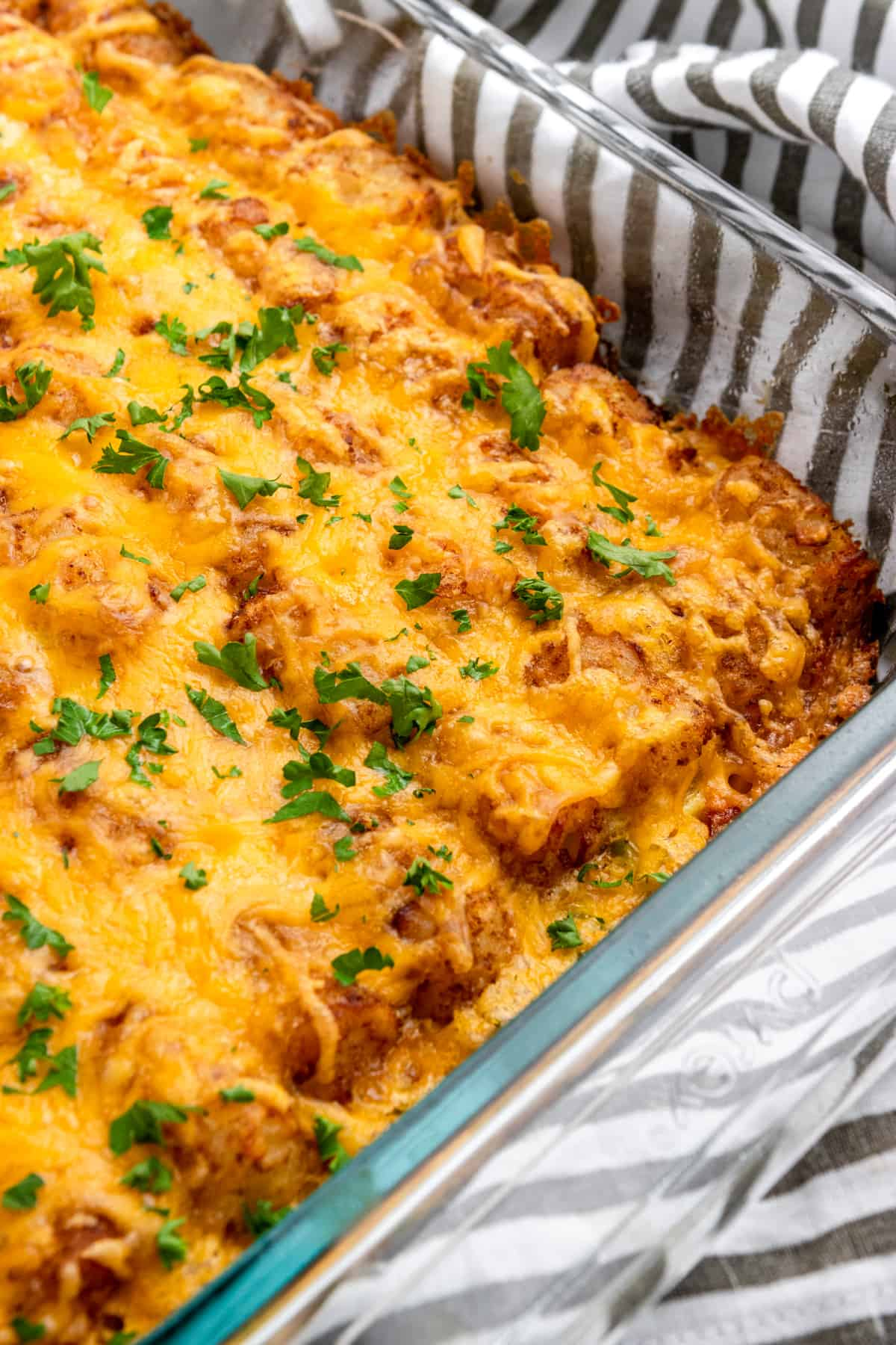 Breakfast casserole with tator tots and cheese on top.