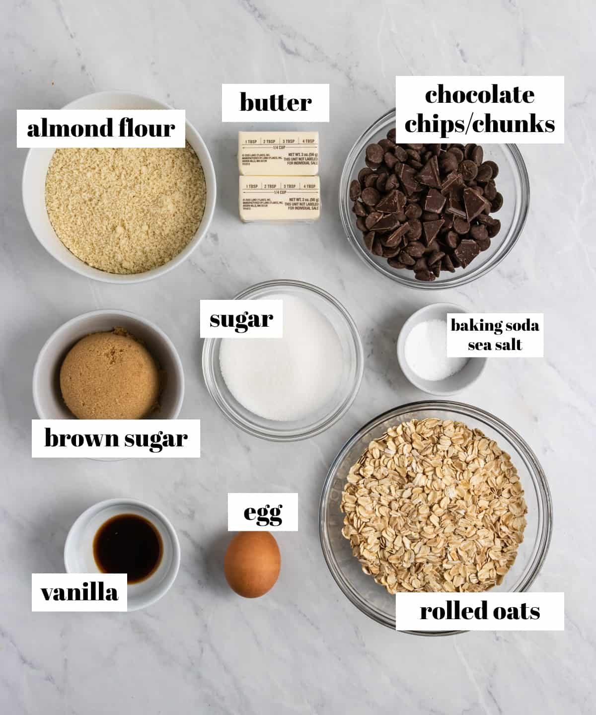 Oats, egg, sugar, butter and other ingredients labeled on counter.