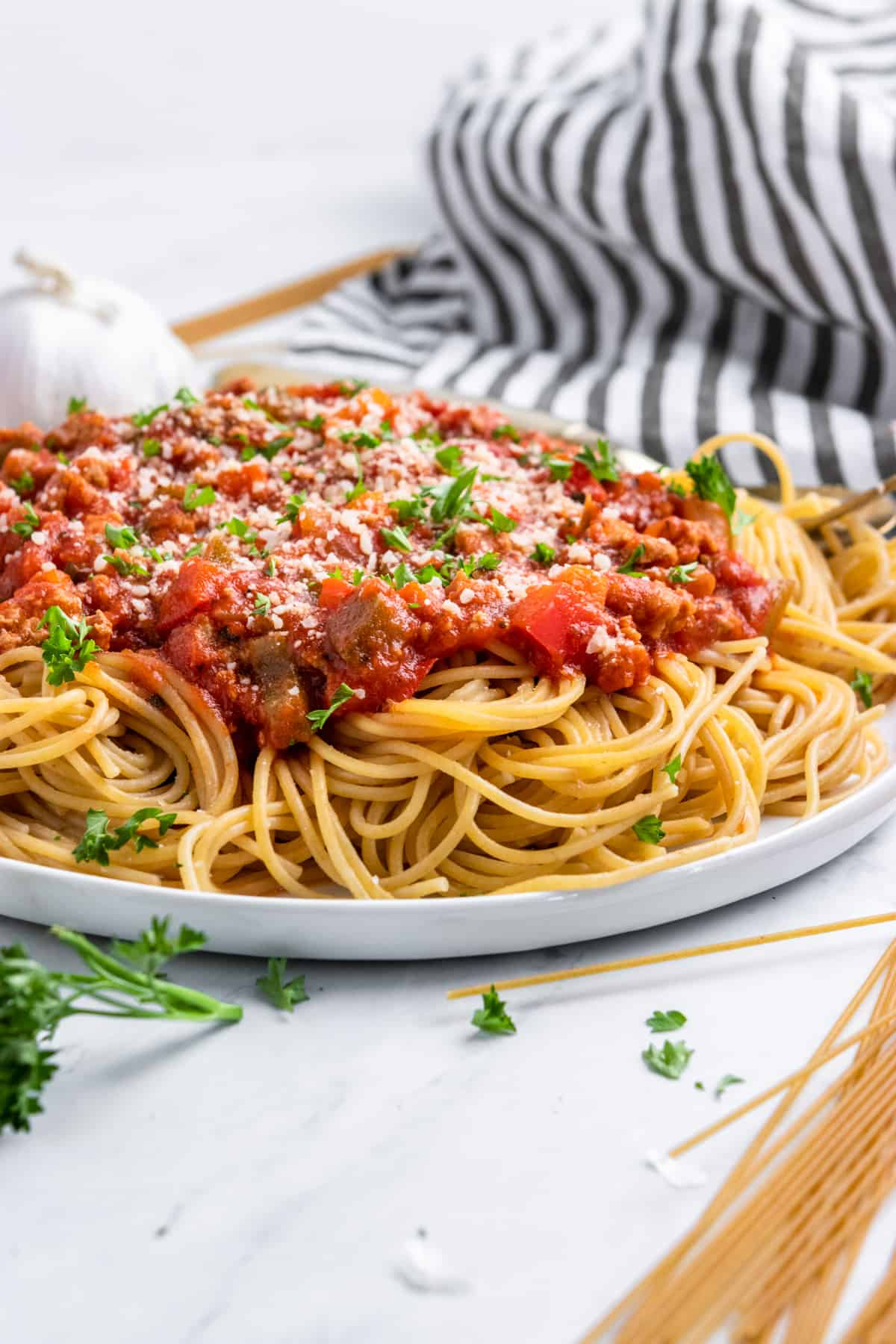 Plate of spaghetti with meat sauce and parmesan and striped napkin.
