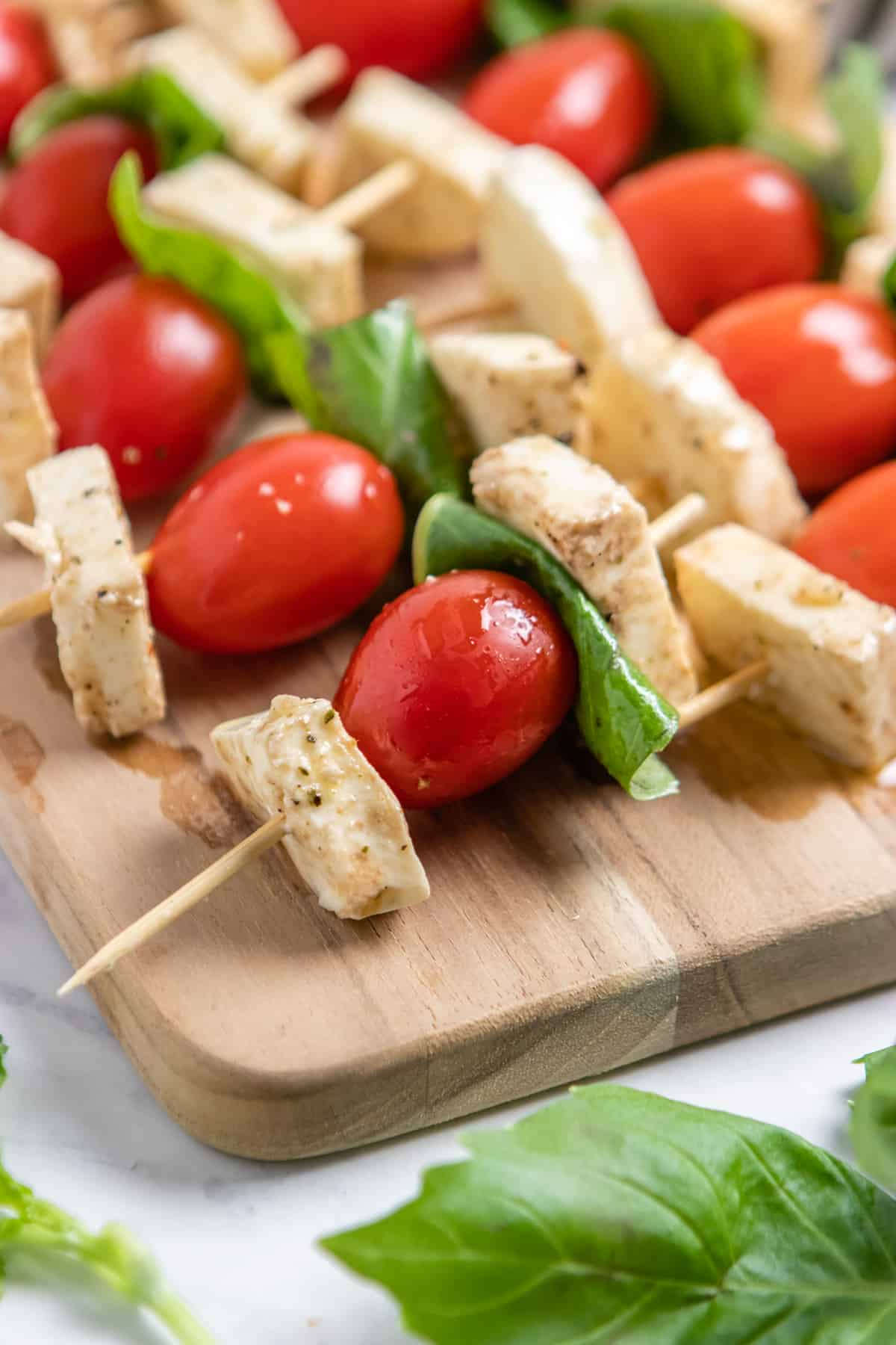 Wood cutting board with marinated mozzarella and tomato skewers with fresh basil.