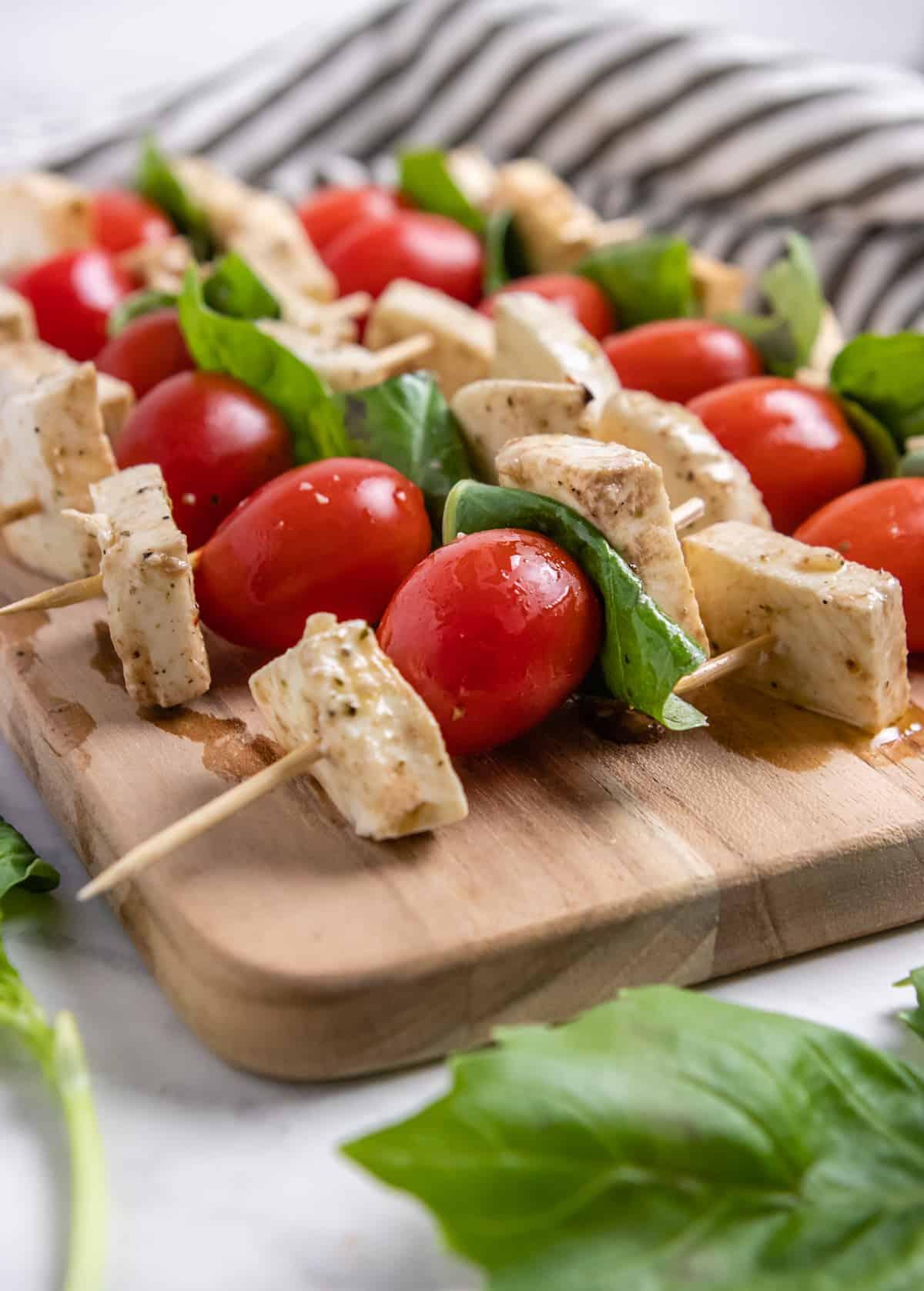 Mozzarella, tomato and basil on toothpicks arranged on wood board.