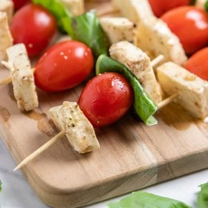 Tomato, mozzarella and basil skewers on wood board.