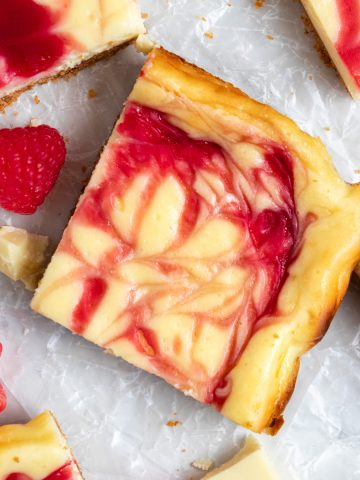 Overhead view of white chocolate cheesecake bars with raspberry swirl on wax paper.