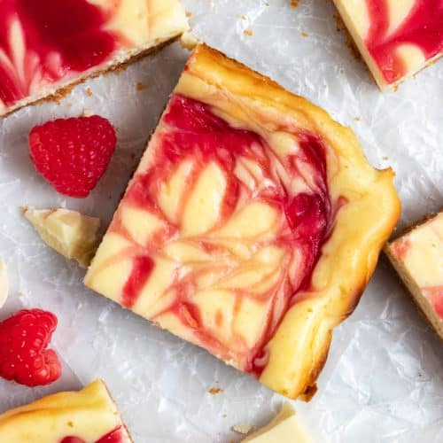 Overhead view of white chocolate cheesecake bars with raspberry swirl on wax paper.