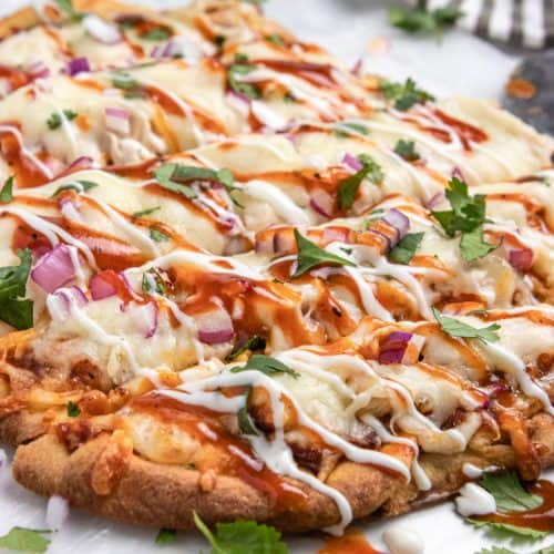 BBQ chicken flatbread with ranch and bbq sauce drizzle and fresh cilantro.