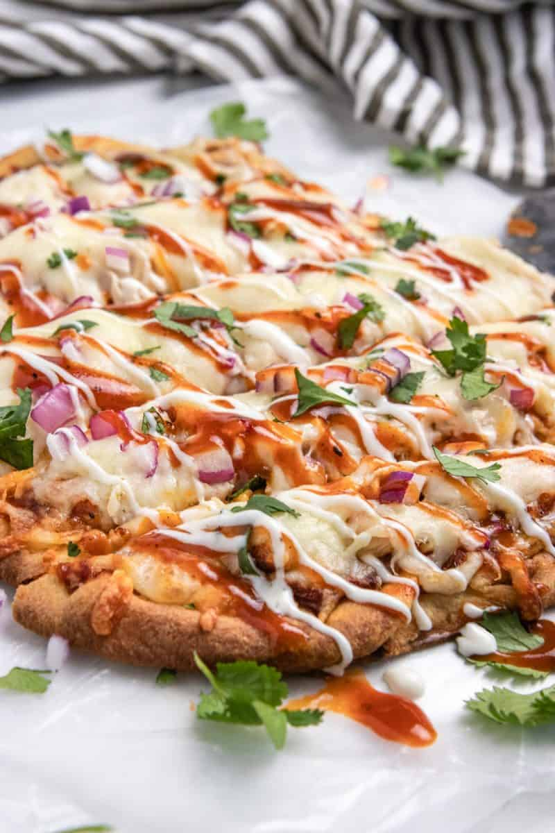 BBQ chicken flatbread on wax paper sliced with ranch and BBQ sauce drizzle.