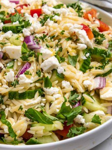 Lemon orzo salad in white bowl with fresh parsley on top.