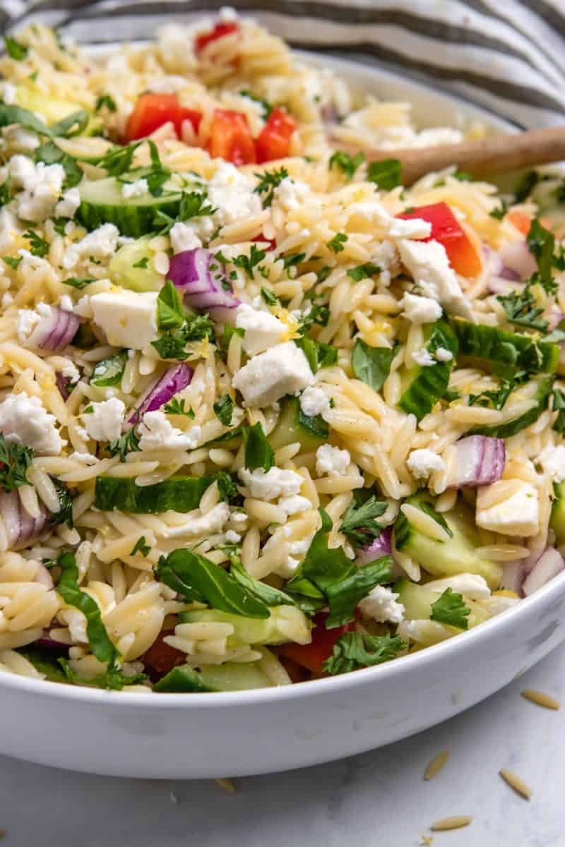Orzo salad with feta, basil, parsley, cucumbers and more in white bowl with spoon.
