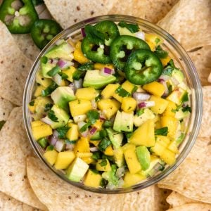 Overhead view of mango avocado salsa in bowl with chips.
