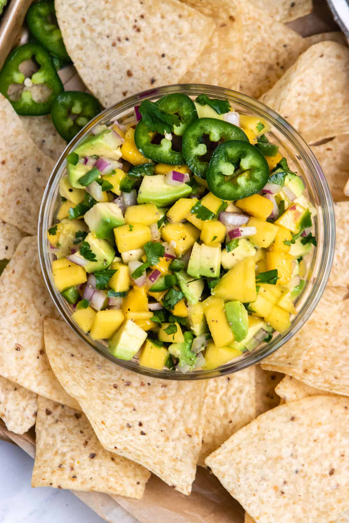 Mango avocado salsa in bowl with jalapeño and chips surrounding.
