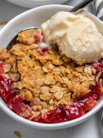 Strawberry crumble in white bowl with ice cream and spoon.