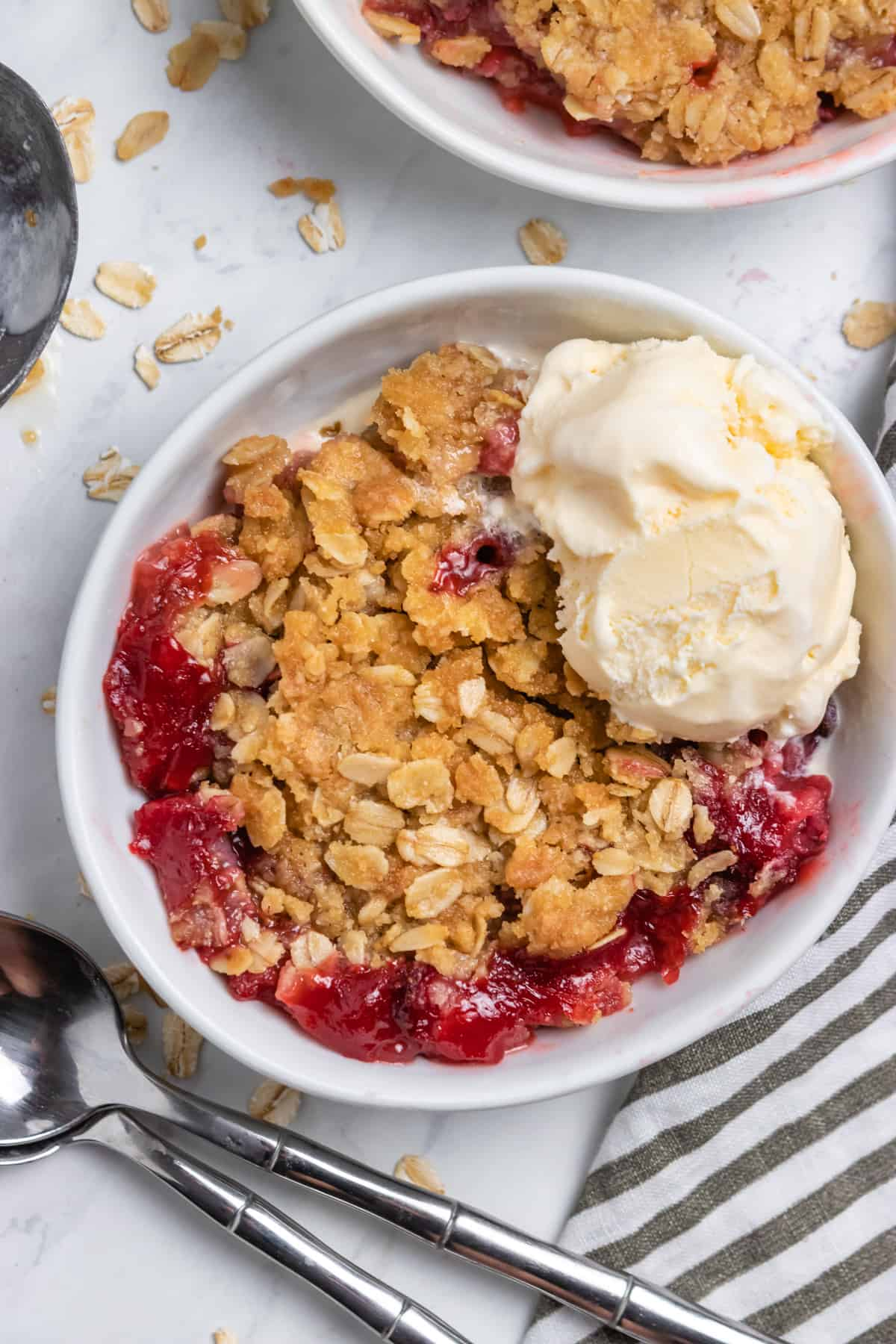 Overhead shot of strawberry crumble in white bowl with spoon and ice cream.