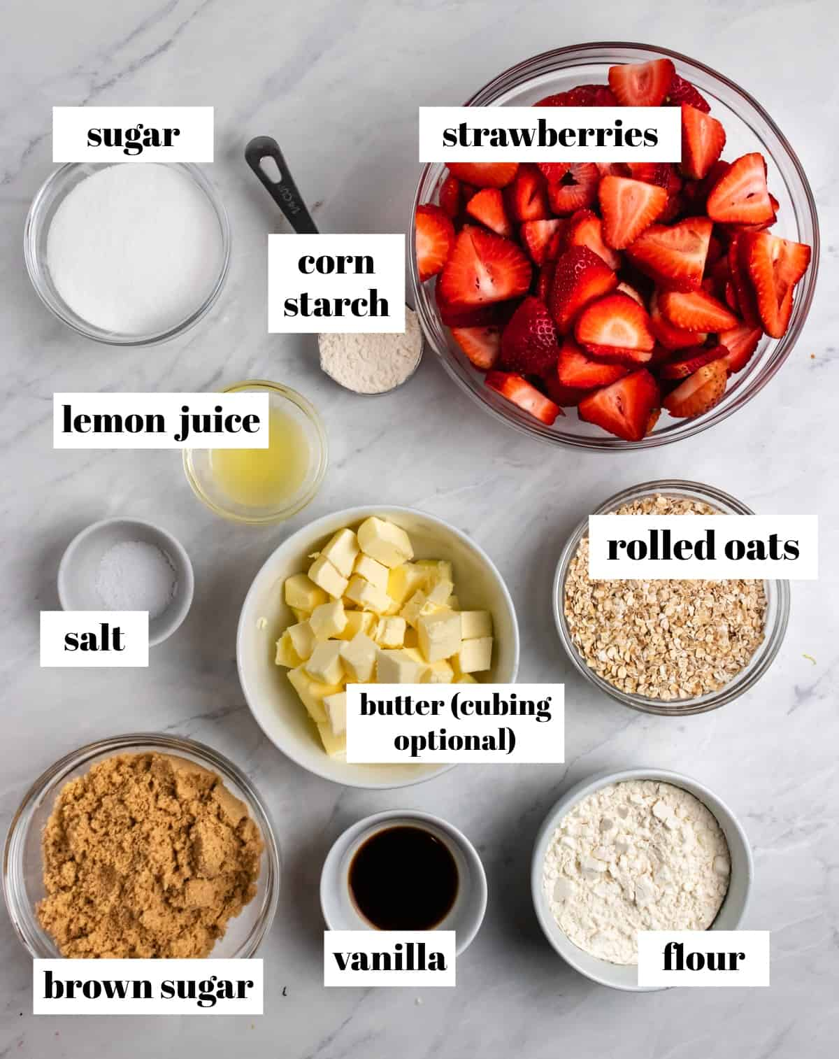 Oats, butter, brown sugar, vanilla and other ingredients labeled on a counter.