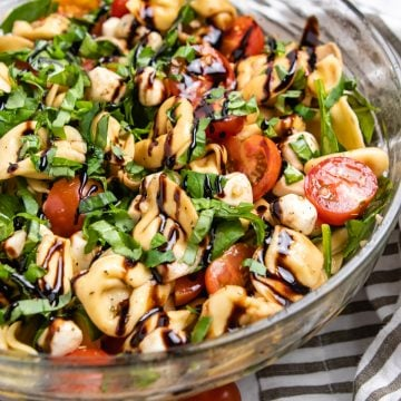 Tortellini caprese pasta salad in bowl with balsamic glaze.
