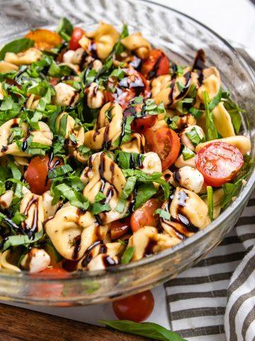 Tortellini caprese pasta salad in bowl with balsamic glaze.