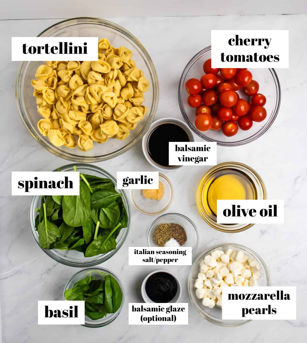 Tomatoes, mozzarella, tortellini, olive oil and other labeled ingredients on counter.