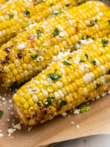 Cilantro lime air fryer corn on the cob sitting on brown parchment.