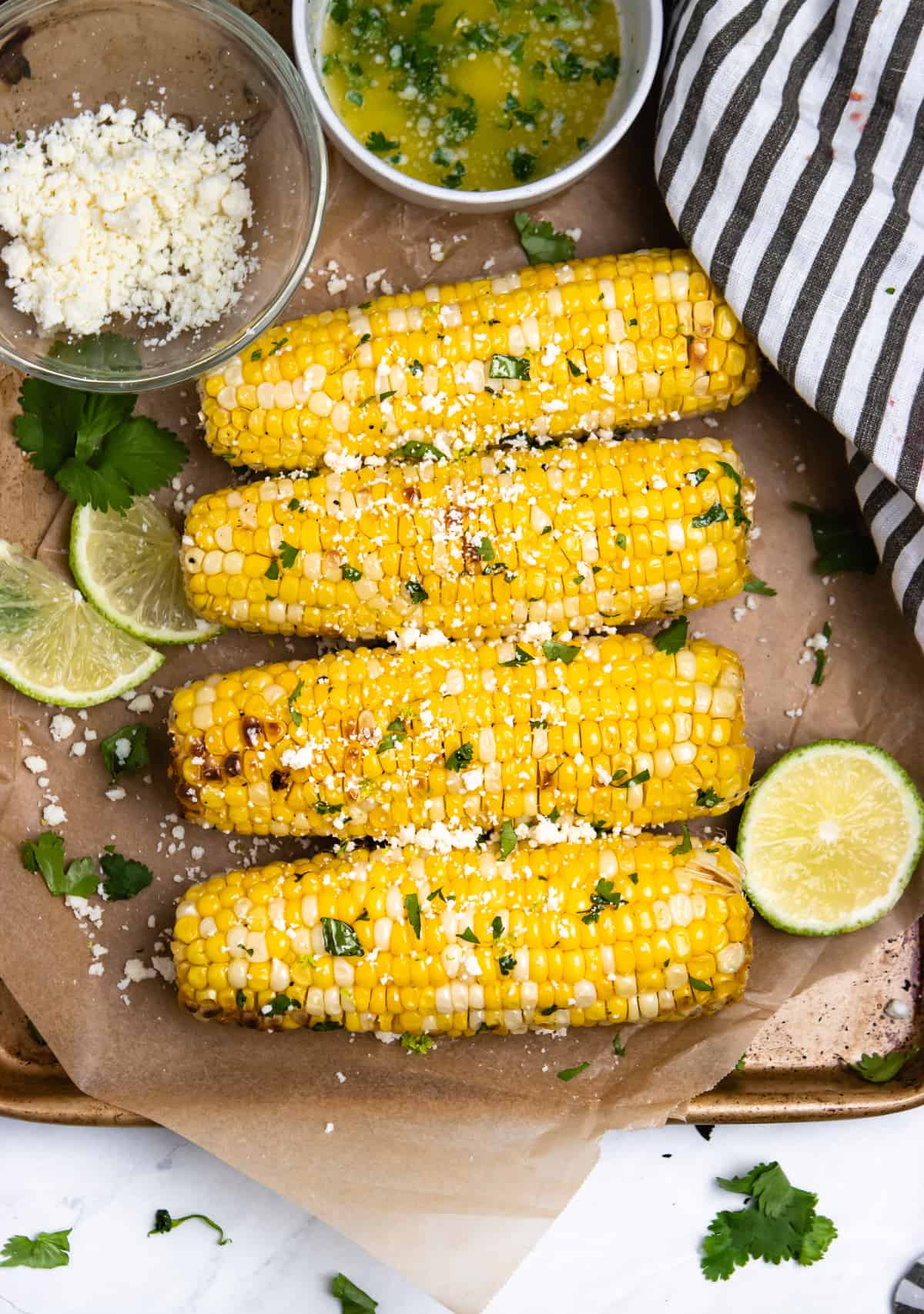 Overview of corn on the cob with limes and cojita cheese on parchment.