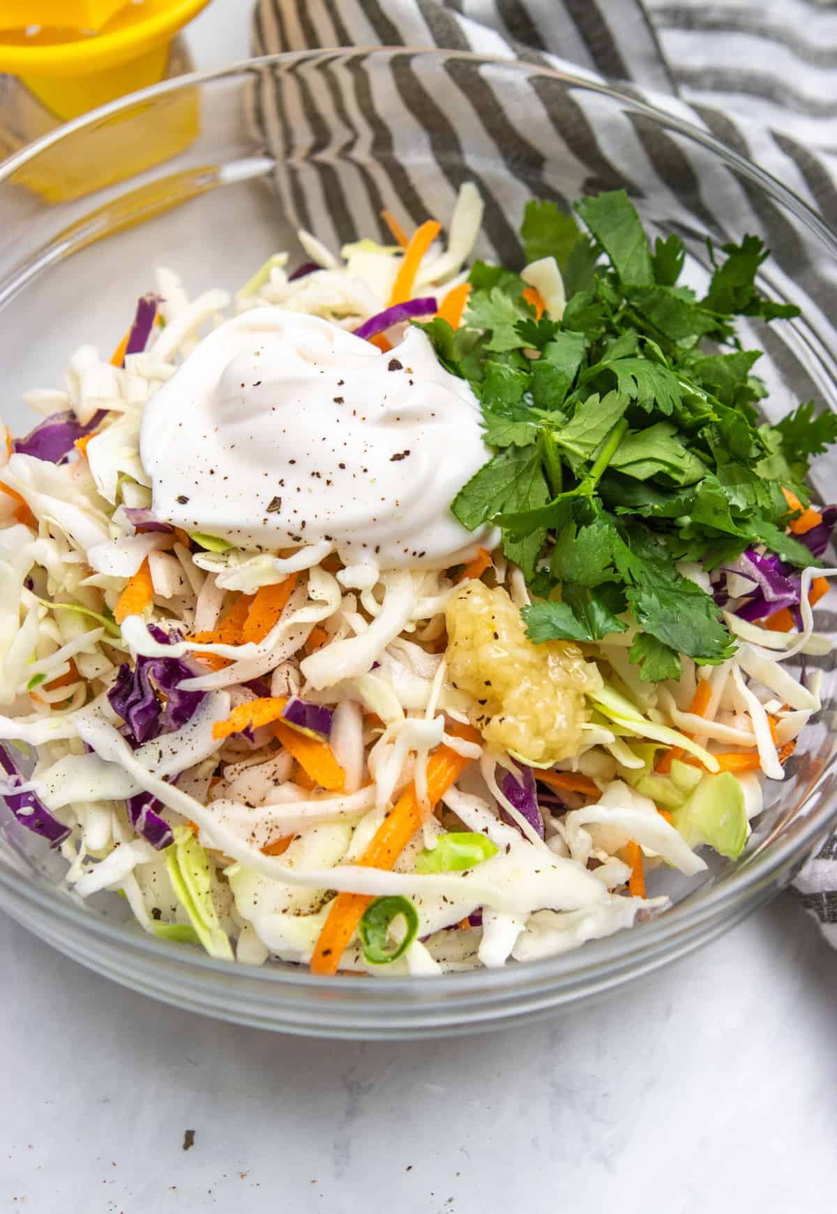 Cilantro lime slaw ingredients in glass mixing bowl.