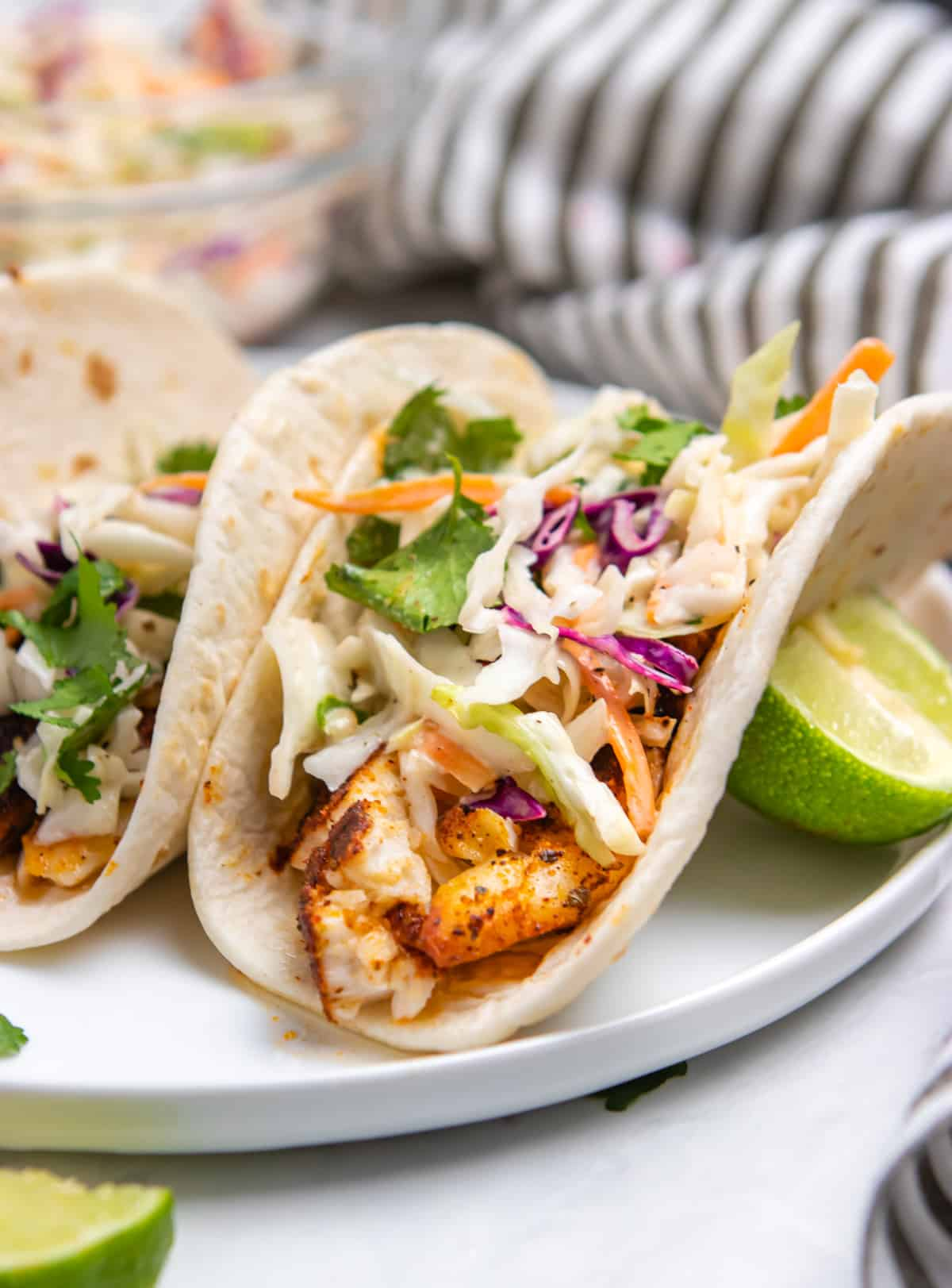 Air fryer fish tacos on white plate with lime.