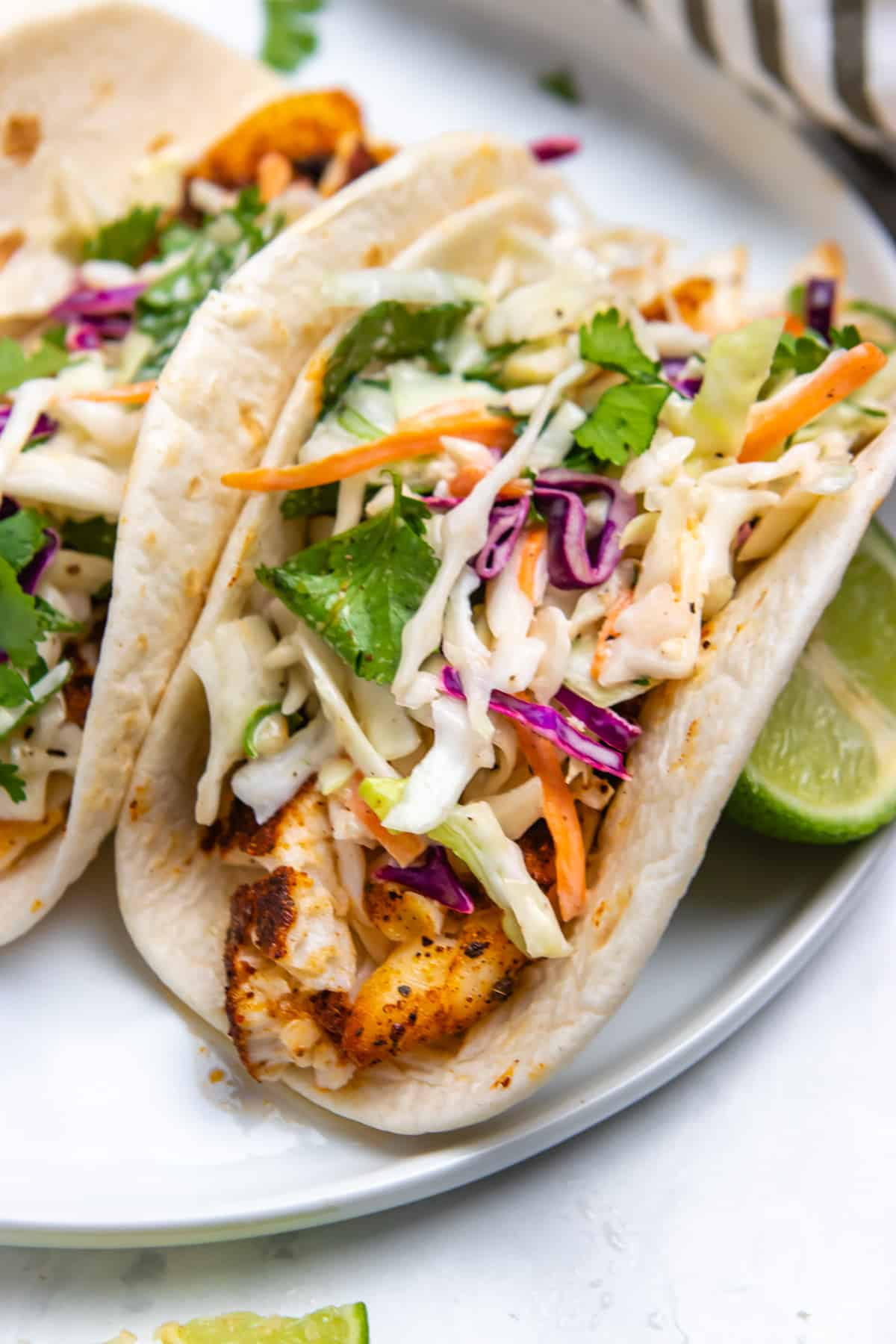 Air fryer fish tacos on white plate with slaw and fresh cilantro.