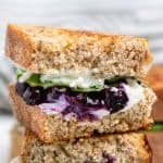 Grilled goat cheese sandwich stacked with blueberries and basil.