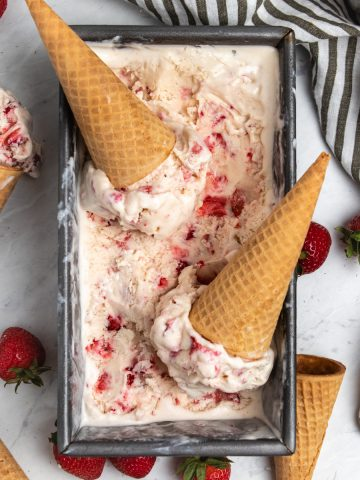 Overhead view of strawberry ice cream in container with cones and fresh strawberries.