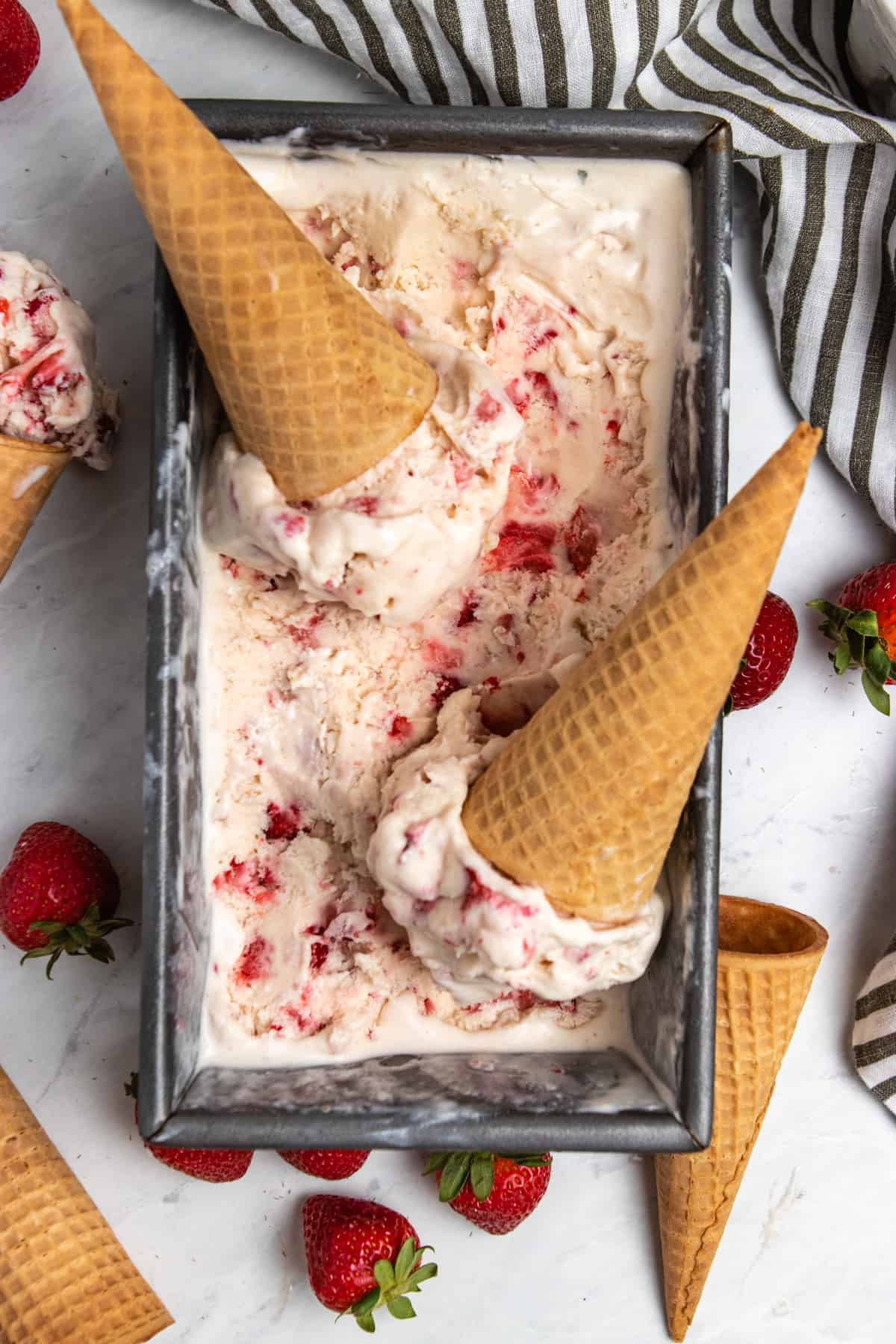 Strawberry ice cream in bread pan loaf with scoops and sugar cones.