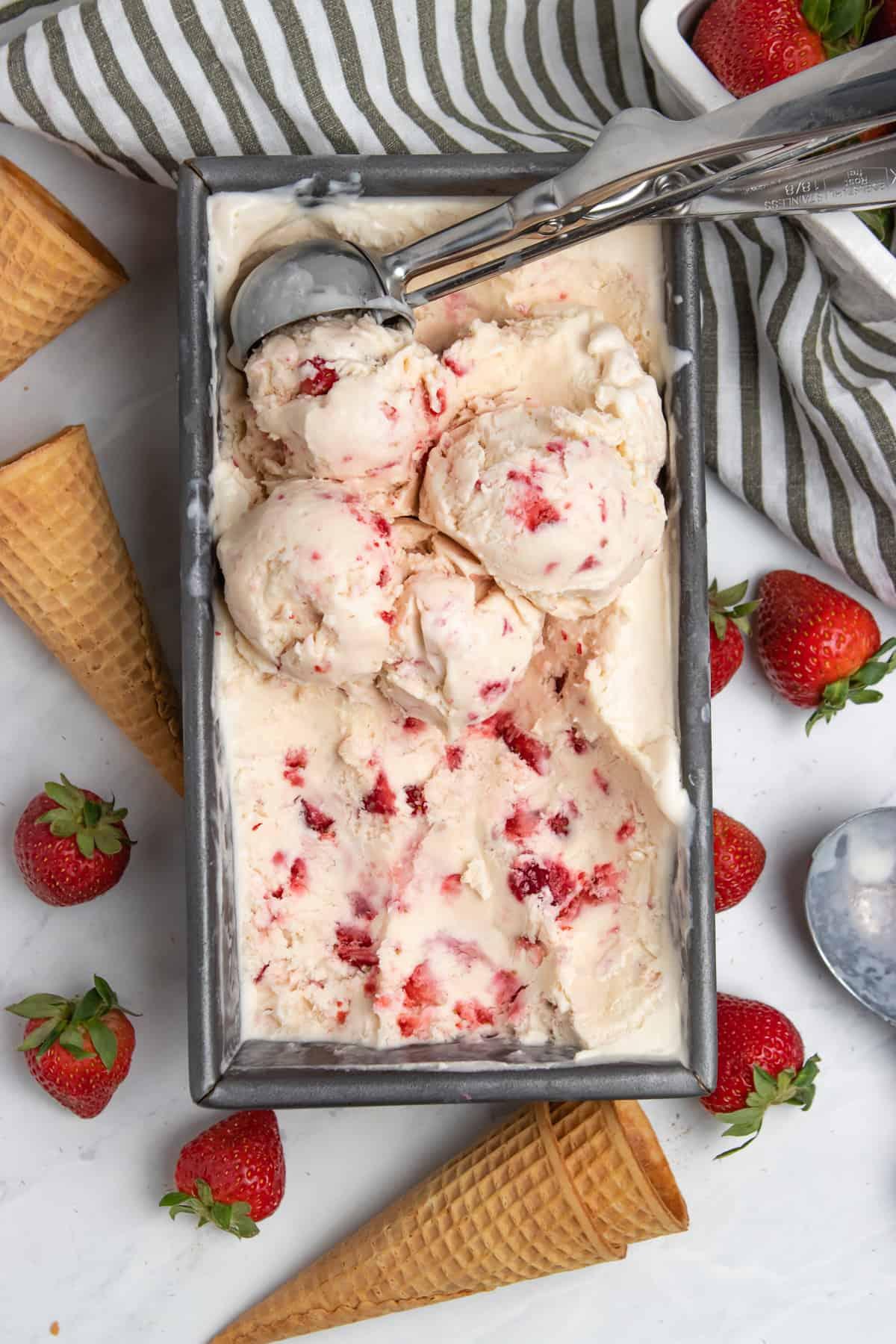 Strawberry ice cream in bread pan with ice cream scoop.