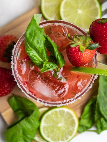 Overhead view of strawberry basil margarita with fresh lime and berries.