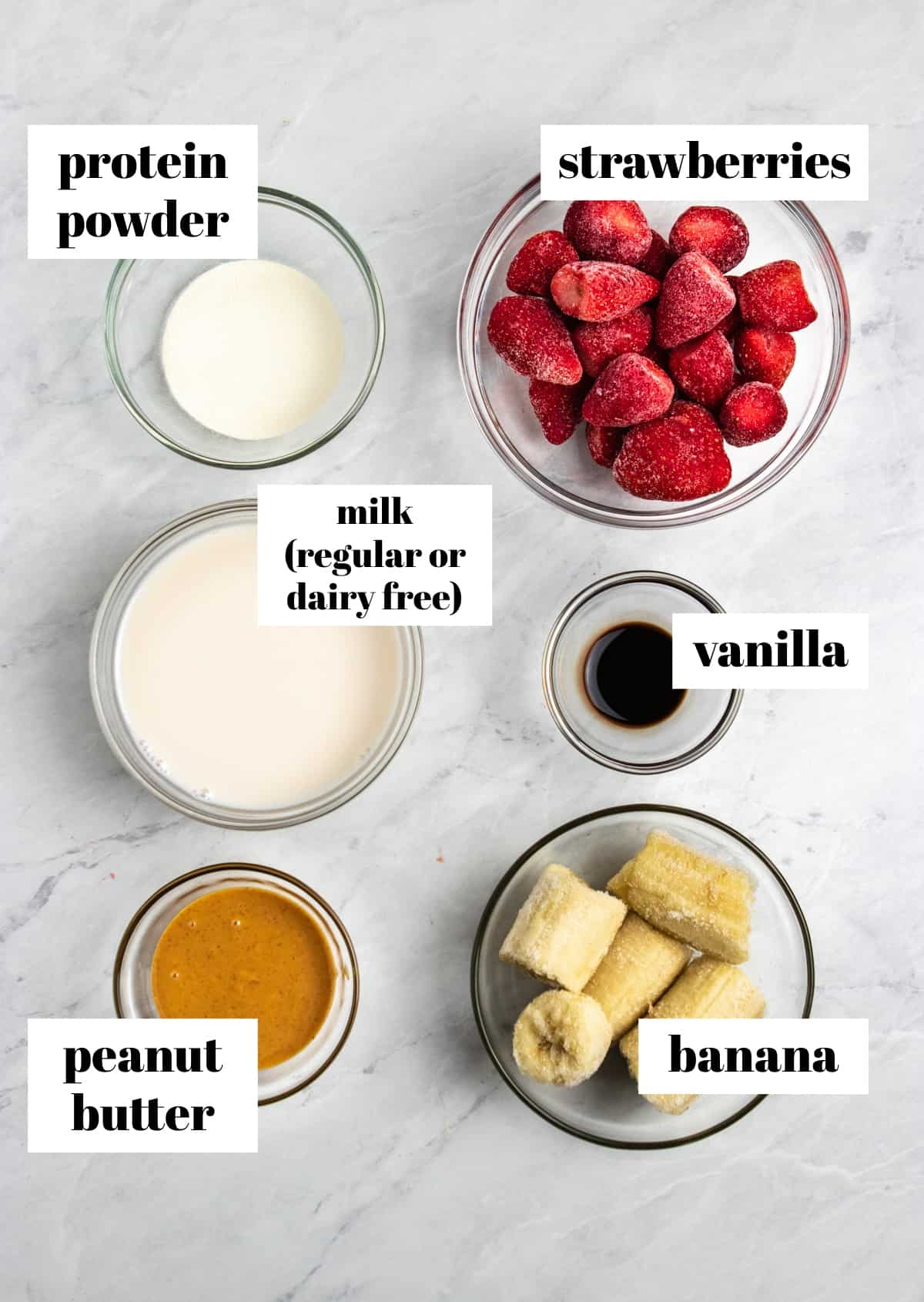Peanut butter, banana, strawberries, vanilla and ingredients labeled on counter.