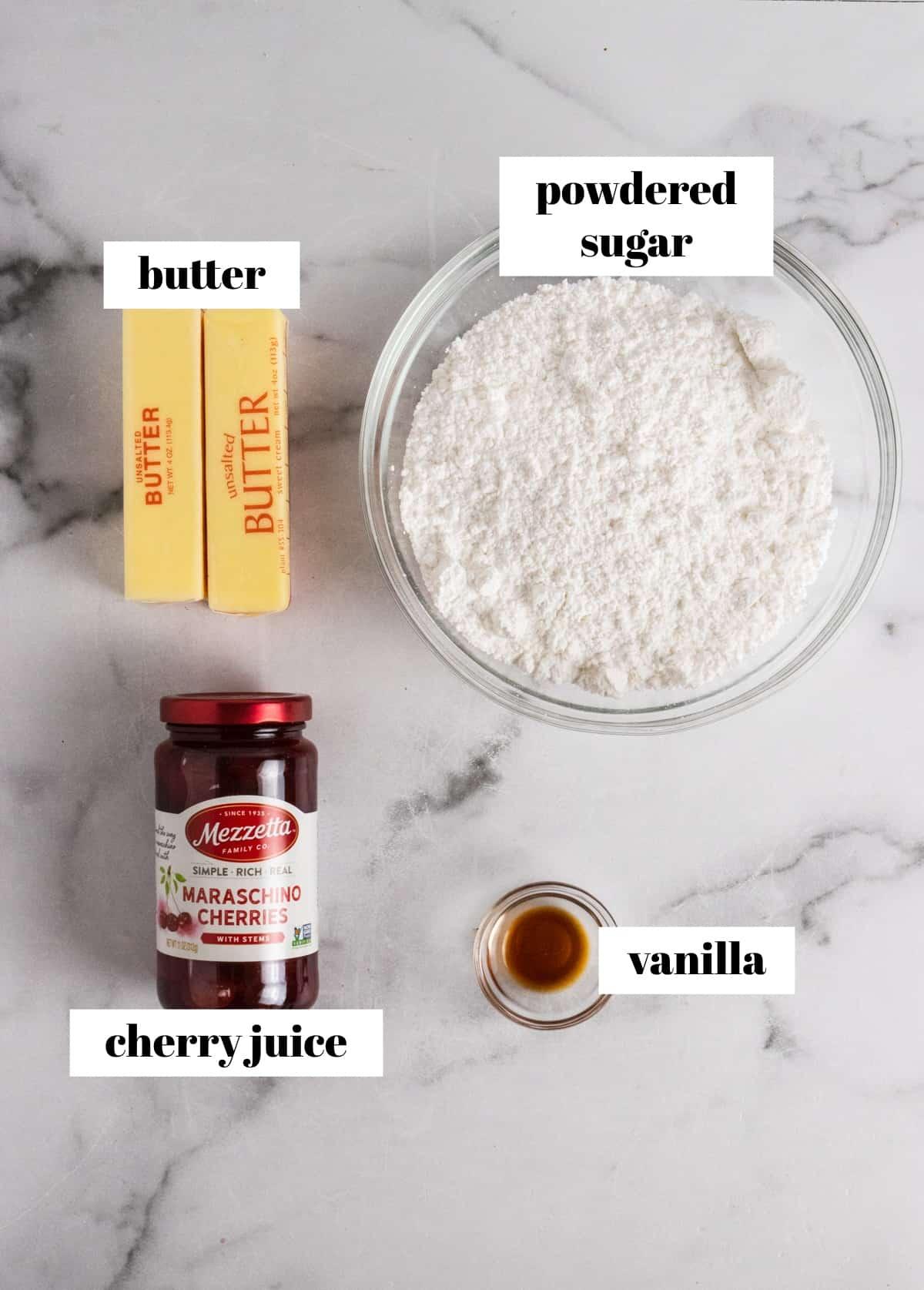 Butter, powdered sugar, vanilla and jar of maraschino cherries labeled on counter.