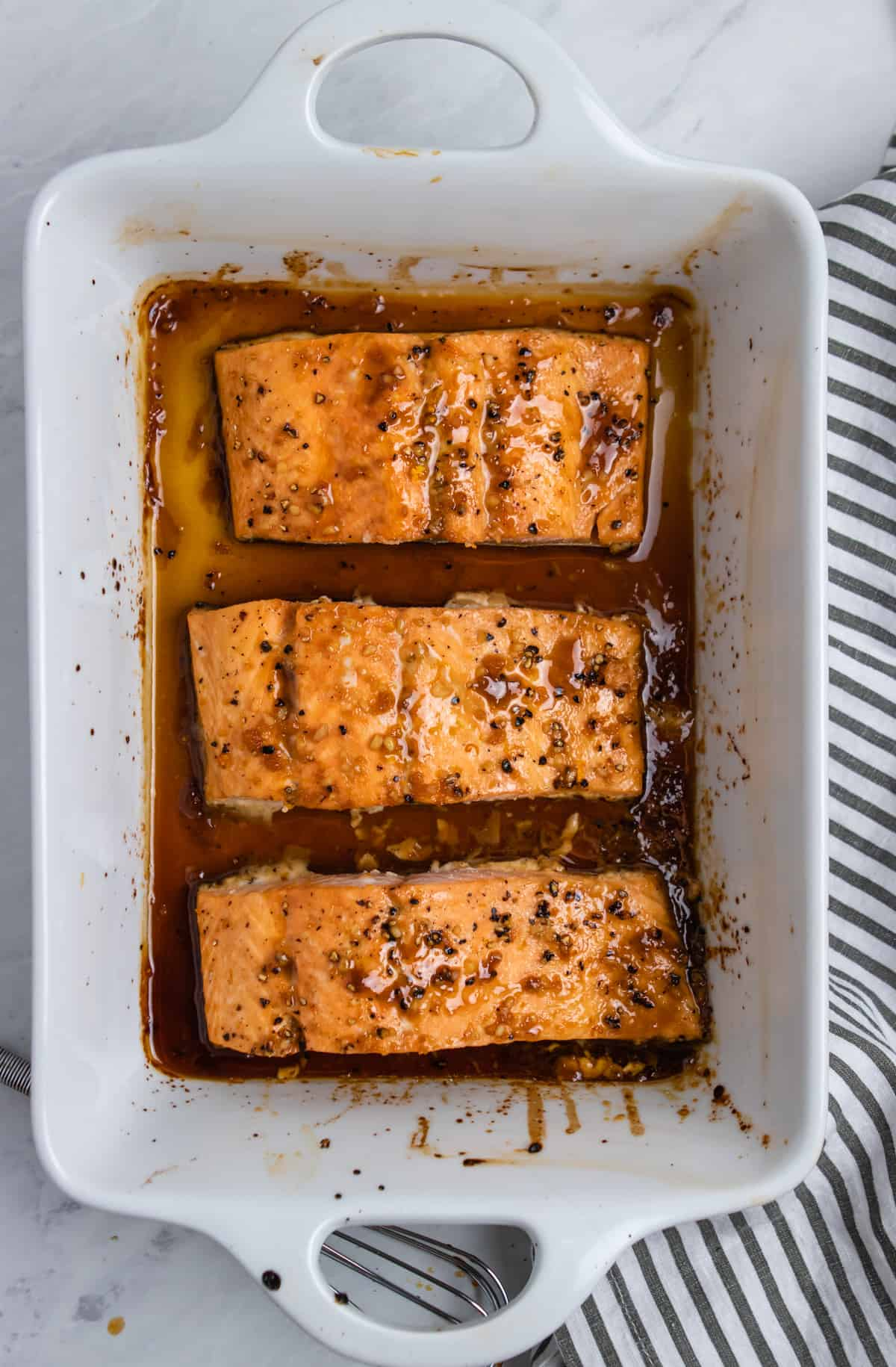Cooked salmon with maple glaze in white dish.
