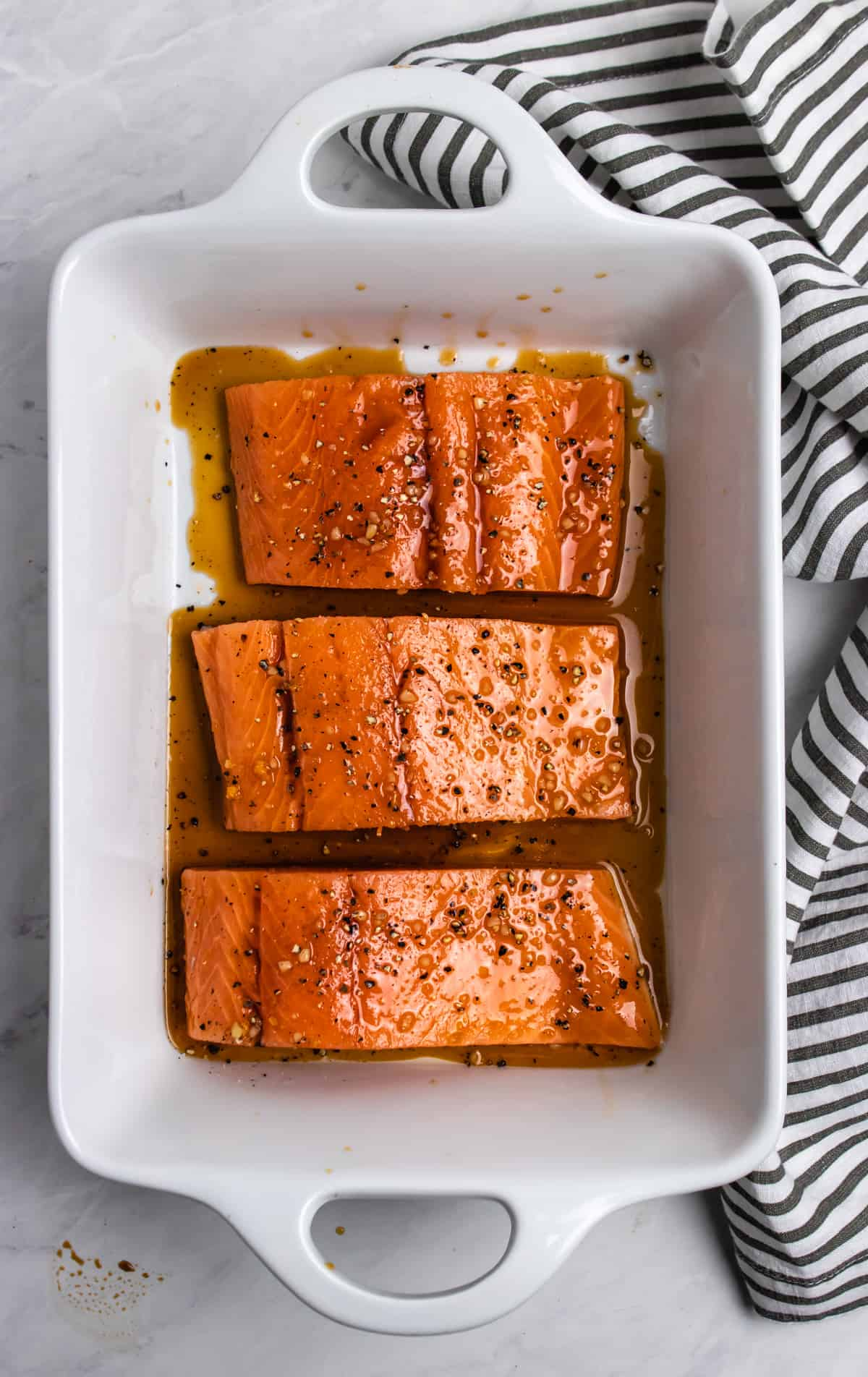 Overhead view of salmon in white dish with glaze on top.