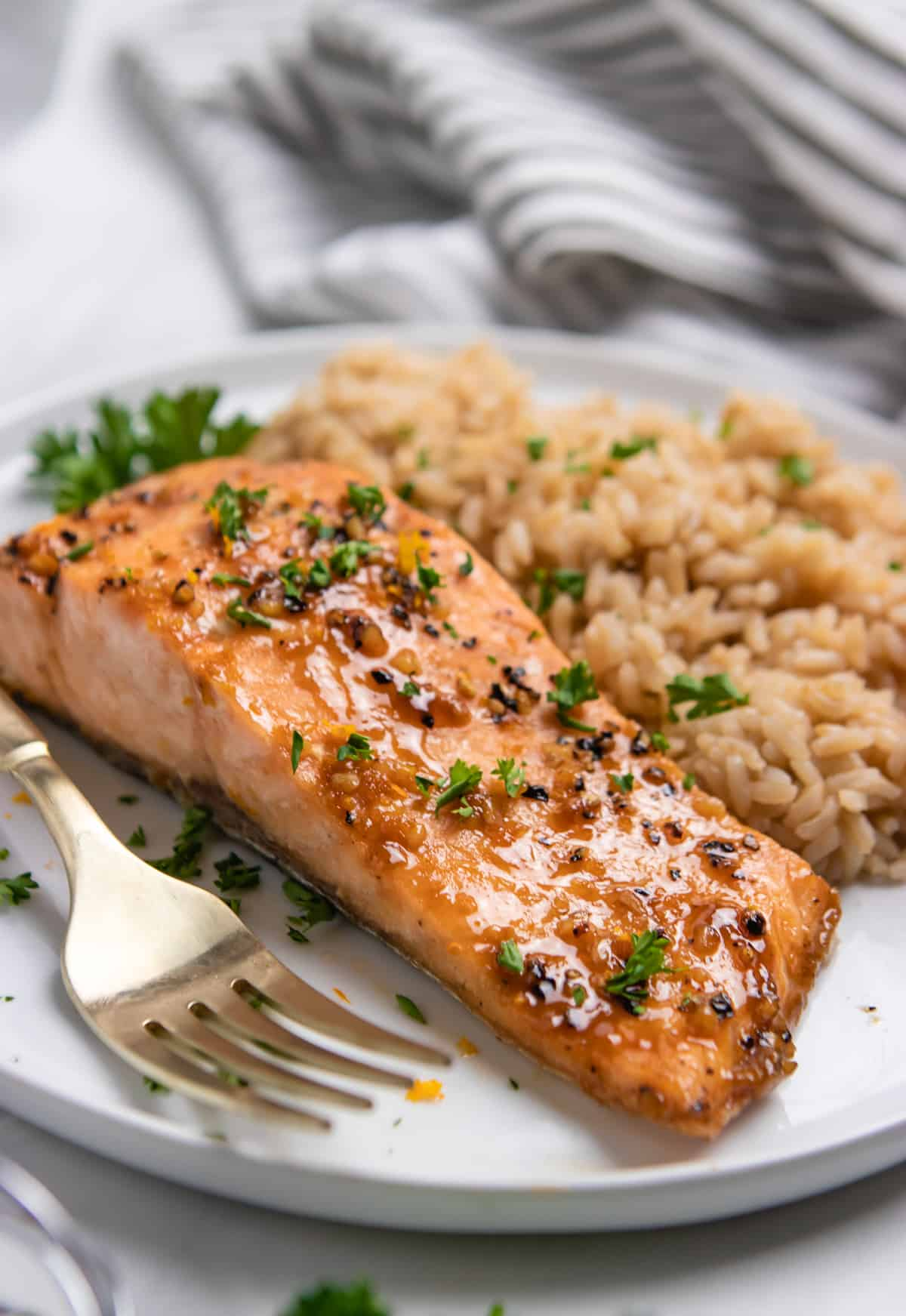 Orange maple glazed salmon on plate with brown rice and fresh parsley on top.
