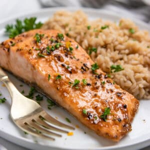 Orange maple glazed baked salmon on white plate with rice.